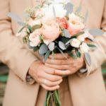 Свадебный букет персикового цвета в руках жениха